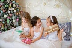 Las muchachas del niño despiertan en su cama por mañana de la Navidad Fotos de archivo