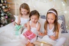 Las muchachas del niño despiertan en su cama por mañana de la Navidad Imagen de archivo
