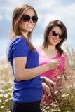 Las muchachas despluman las flores en un prado Fotos de archivo