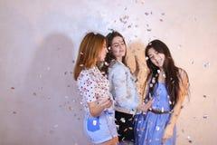 Las muchachas divertidas presentan in camera con sonrisas en sus caras y se colocan Imagen de archivo libre de regalías