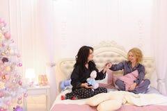 Las muchachas divertidas salen a la más lleno en la cama para la música fresca en smartph Fotografía de archivo libre de regalías