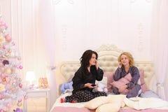 Las muchachas divertidas salen a la más lleno en la cama para la música fresca en smartph Fotos de archivo libres de regalías