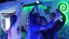 Las muchachas divertidas se divierten y toman las fotos en el artilugio en el gallina-partido del club nocturno, almacen de video