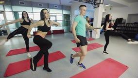 Las muchachas divertidas trabajan con un instructor en gimnasio de la aptitud almacen de video