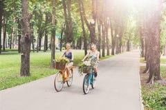 Las muchachas elegantes del boho feliz montan juntas en las bicicletas en parque Imagen de archivo libre de regalías
