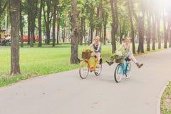 Las muchachas elegantes del boho feliz montan juntas en las bicicletas en parque Fotografía de archivo libre de regalías