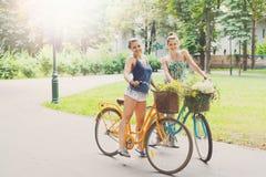 Las muchachas elegantes del boho feliz montan juntas en las bicicletas en parque Foto de archivo