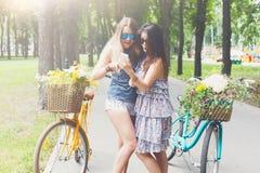 Las muchachas elegantes del boho feliz montan juntas en las bicicletas en parque Fotos de archivo libres de regalías