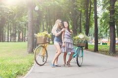 Las muchachas elegantes del boho feliz montan juntas en las bicicletas en parque Fotos de archivo