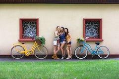 Las muchachas elegantes del boho feliz presentan con las bicicletas cerca de fachada de la casa Foto de archivo