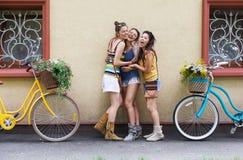 Las muchachas elegantes del boho feliz presentan con las bicicletas cerca de fachada de la casa Foto de archivo libre de regalías