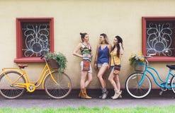 Las muchachas elegantes del boho feliz presentan con las bicicletas cerca de fachada de la casa Imagenes de archivo