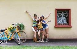 Las muchachas elegantes del boho feliz presentan con las bicicletas cerca de fachada de la casa Imágenes de archivo libres de regalías