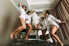 Las muchachas emocionales con una novia saltan en la cama Fotografía de archivo libre de regalías