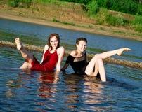 Las muchachas en alineada mojada se sientan en agua Imagen de archivo libre de regalías