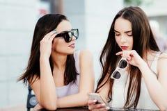 Las muchachas en café están mirando el teléfono Imagen de archivo libre de regalías