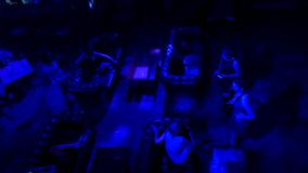Las muchachas en club con el azul encienden la visión superior Silueta de la mujer en el fondo azul, vestido que agita como fluye fotografía de archivo libre de regalías