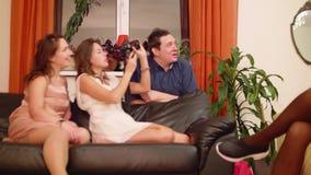 Las muchachas en disfraces y hombre se sientan en el sofá y hacen las fotos almacen de video