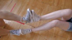 Las muchachas en el gimnasio realizan el ejercicio 'bici 'de los pares que descansa sus pies cara a cara atletismo metrajes