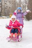 Las muchachas en el patio de montar un trineo de la nieve disfrutan Fotos de archivo