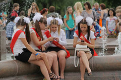 Las muchachas en uniforme escolar, los arcos y el ` de la cinta gradúan el ` en la celebración de la última llamada en Stalingrad Imagenes de archivo