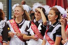 Las muchachas en uniforme escolar soviético, los arcos y el ` de la cinta gradúan el ` en la celebración de la última llamada en  Imagen de archivo