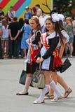Las muchachas en uniforme escolar soviético, los arcos y el ` de la cinta gradúan el ` en la celebración de la última llamada en  Foto de archivo libre de regalías