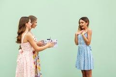 Las muchachas encantadoras están dando a su amigo adulto joven hermoso un presente, la mujer está sonriendo y maravilla Imagen de archivo libre de regalías