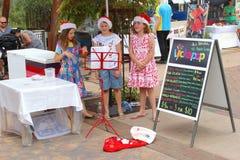 Las muchachas están cantando canciones de la Navidad en Alice Springs, Australia fotografía de archivo