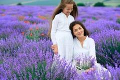 Las muchachas están en el campo de flor de la lavanda, paisaje hermoso del verano imagenes de archivo