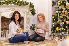 Las muchachas están esperando sorpresas agradables del Año Nuevo y son sittin Foto de archivo libre de regalías