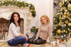 Las muchachas están esperando sorpresas agradables del Año Nuevo y son sittin Imagen de archivo libre de regalías