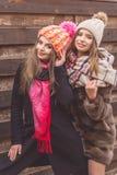 Las muchachas están llevando la ropa del invierno cerca de la pared de madera Imagen de archivo