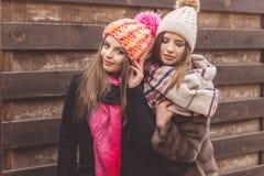 Las muchachas están llevando la ropa del invierno cerca de la pared de madera Fotografía de archivo libre de regalías
