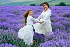 Las muchachas est?n en el campo de flor de la lavanda, paisaje hermoso del verano imagenes de archivo