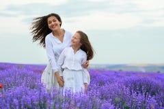 Las muchachas est?n en el campo de flor de la lavanda, paisaje hermoso del verano fotografía de archivo