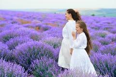 Las muchachas est?n en el campo de flor de la lavanda, paisaje hermoso del verano foto de archivo libre de regalías