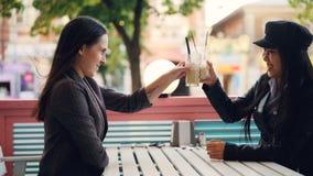 Las muchachas felices caucásicas y los mejores amigos asiáticos se están sentando en la tabla en café de la calle que hablan y lo metrajes