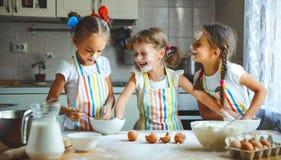 Las muchachas felices de los niños de las hermanas cuecen las galletas, amasan la pasta, ingenio del juego imagenes de archivo