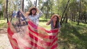 Las muchachas felices del americano ríen y bailan con la bandera de los E.E.U.U. al aire libre, viajando almacen de metraje de vídeo