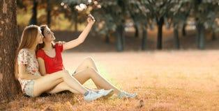Las muchachas felices hacen la foto en Autumn Meadow Foto de archivo