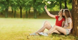 Las muchachas felices hacen la foto en el prado del verano Fotografía de archivo libre de regalías