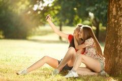 Las muchachas felices hacen la foto en el prado del verano Foto de archivo libre de regalías