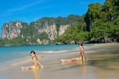 Las muchachas felices juegan en el mar en la playa tropical Foto de archivo libre de regalías