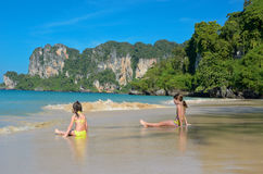 Las muchachas felices juegan en el mar en la playa tropical Imagen de archivo libre de regalías