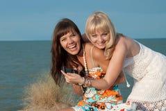 Las muchachas felices llegaron en la playa Imágenes de archivo libres de regalías