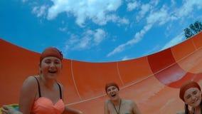 Las muchachas felices que van abajo de un waterslide en el agua parquean almacen de metraje de vídeo