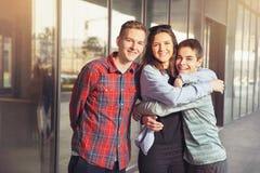 Las muchachas felices y los muchachos adolescentes que se divierten buen miden el tiempo al aire libre Foto de archivo libre de regalías
