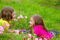 Las muchachas gemelas felices de la hermana que juegan el la primavera florecen el prado Foto de archivo libre de regalías