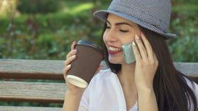 Las muchachas hablan en el teléfono en el banco metrajes